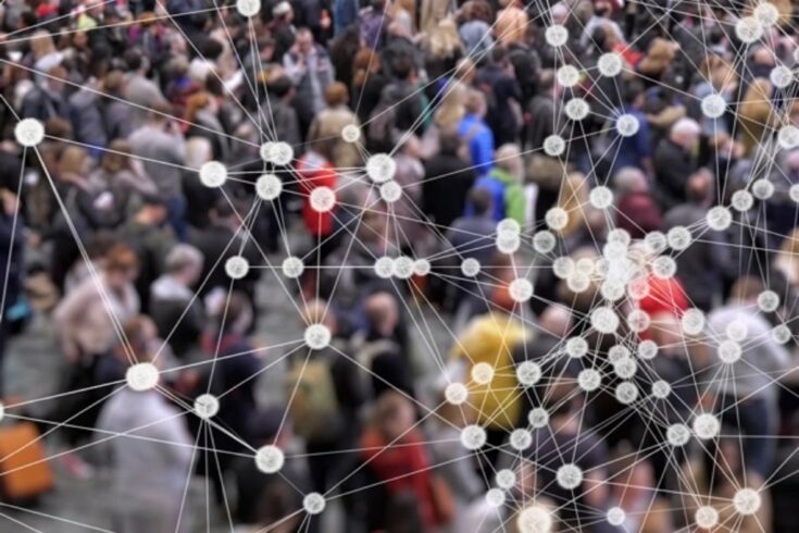 A crowd of people with a network of cells in the front of the frame