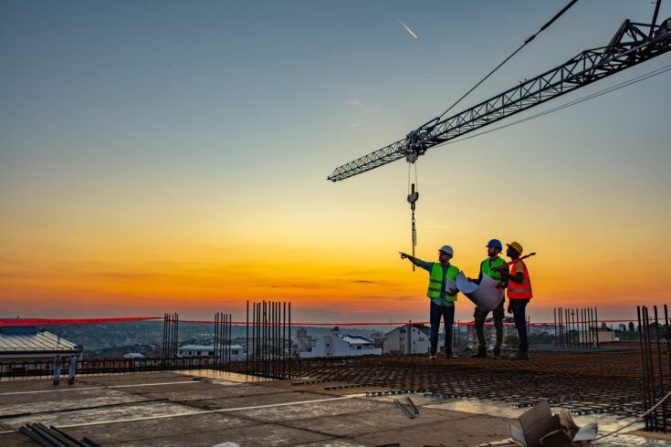 Workers on a construction site with a crane