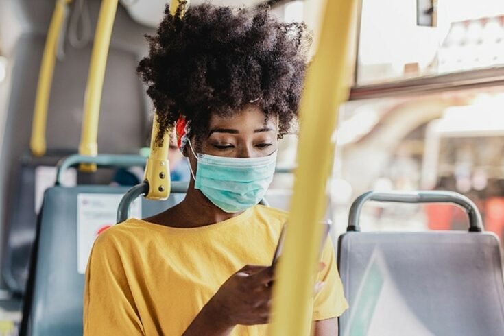 Woman wearing a face mask on a bus