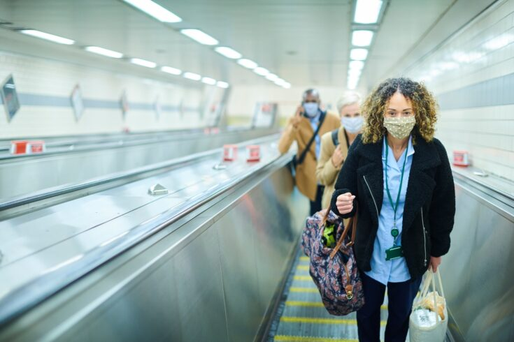 A female commuter on her way to work by underground wearing a face mask