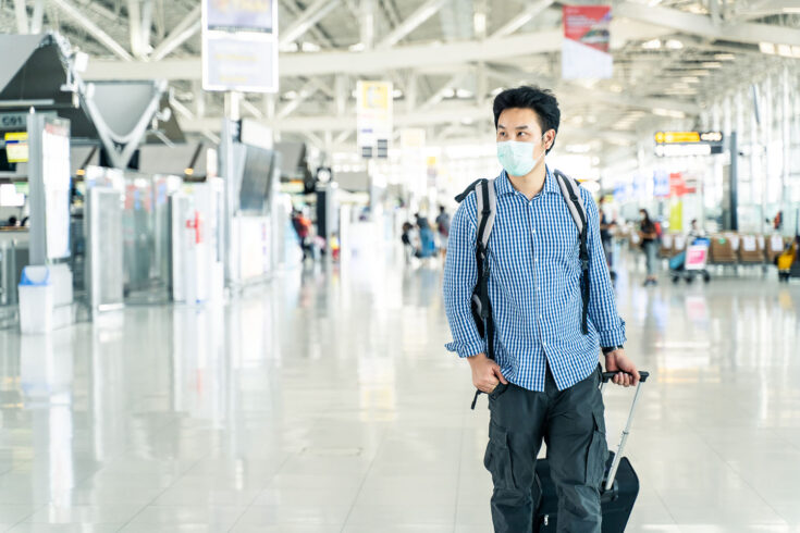 Asian traveler with luggage, wearing a face mask and looking at the time table in the departure terminal in an airport during the COVID-19 virus pandemic.