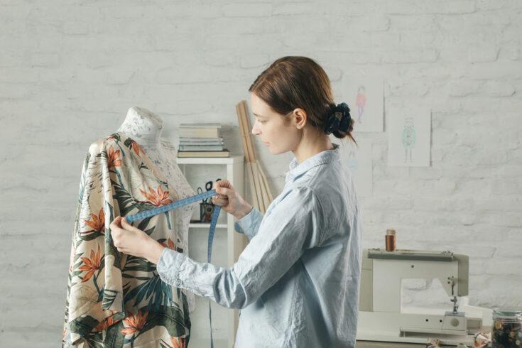 Tailor adjusts garment design on mannequin in workshop.