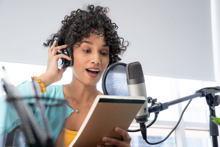 Young Black woman reading her script while doing her podcast show