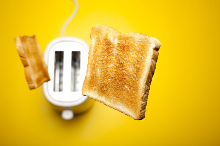 Photograph of fresh toast bread jumping out of the toaster.