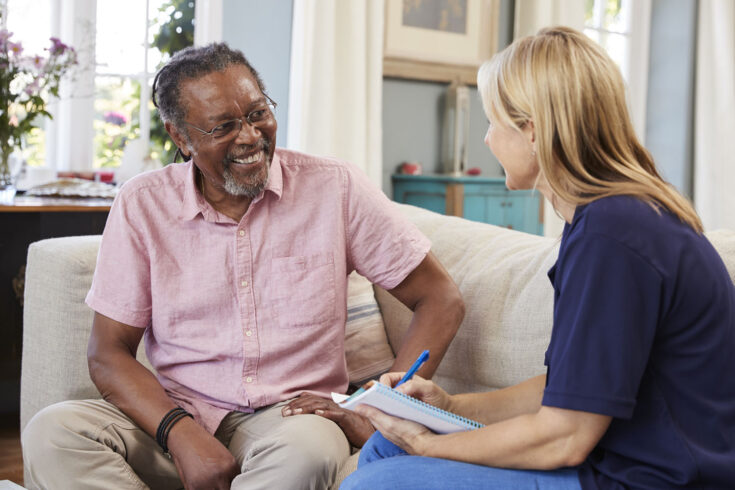 Female support worker visits senior man at home.