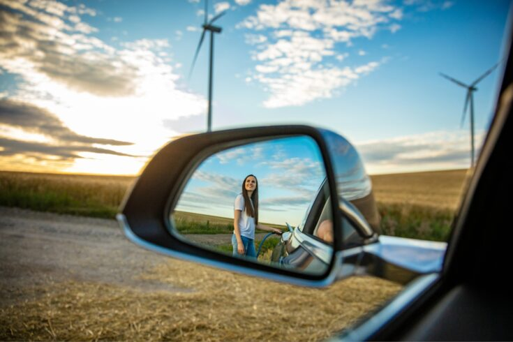 Reflection of young woman charging electric car on road in rural scenery with wind turbines at sunset