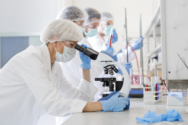 Scientists studying a virus, looking through microscope