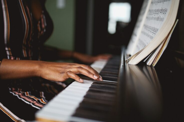 A black pianist's hands playing a piano