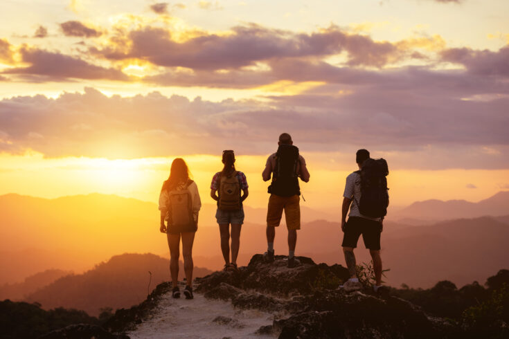 Four people's silhouettes on mountain top looks at sunset