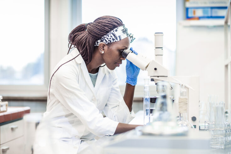 Female Scientist Working in The Laboratory, Using a Microscope