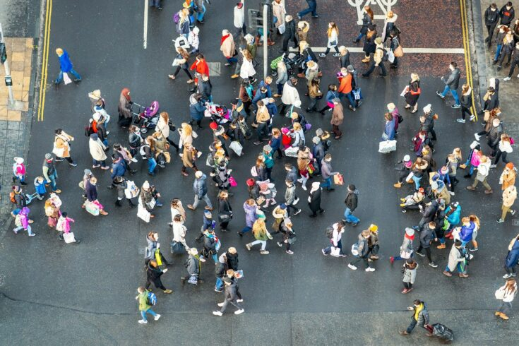 An image, taken from above, of people crossing the road at a busy junction