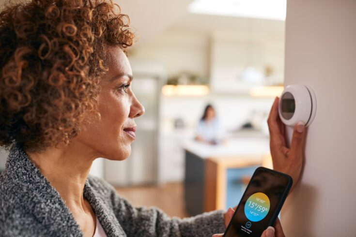 Woman using app on smart phone to control digital central heating thermostat at home