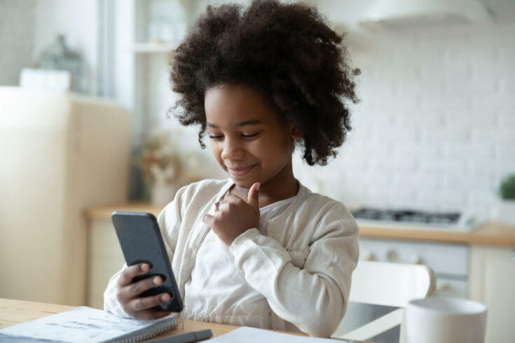 Little biracial girl looking at phone