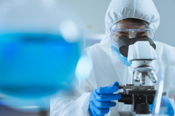 Young Asian handsome man scientist adjust focus and use Microscope to looking biochemical cell in laboratory. Doctor and scientist work in laboratory pandemic of corona virus, COVID19 concept