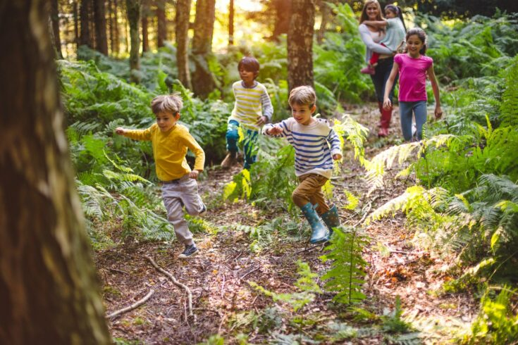 Group of children at running through a woodland with their guide/teacher walking behind them