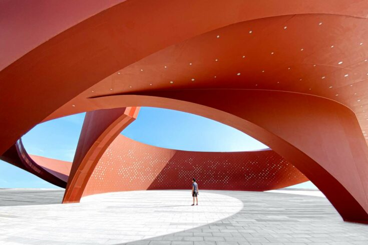 A person in a red curved abstract architectural space