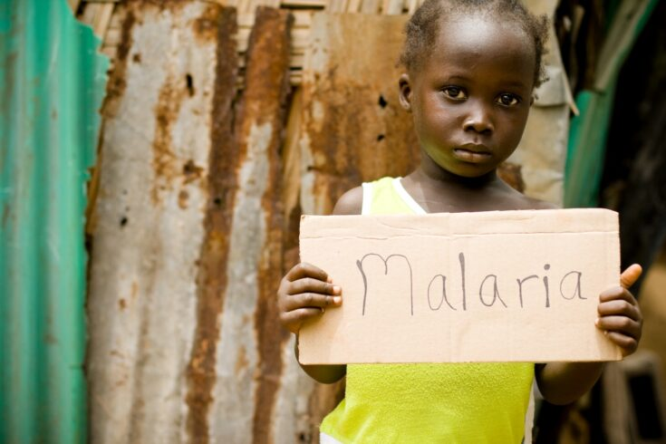 An African girl holding a sign with 'Malaria' written on it