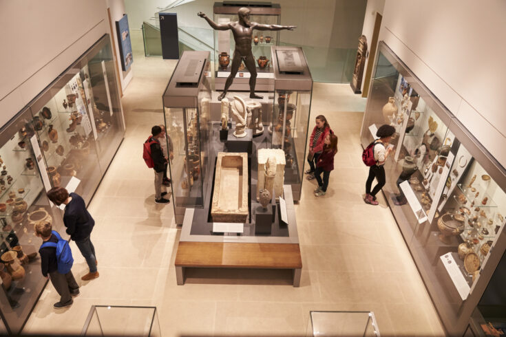 Overhead View Of Busy Museum Interior With Visitors