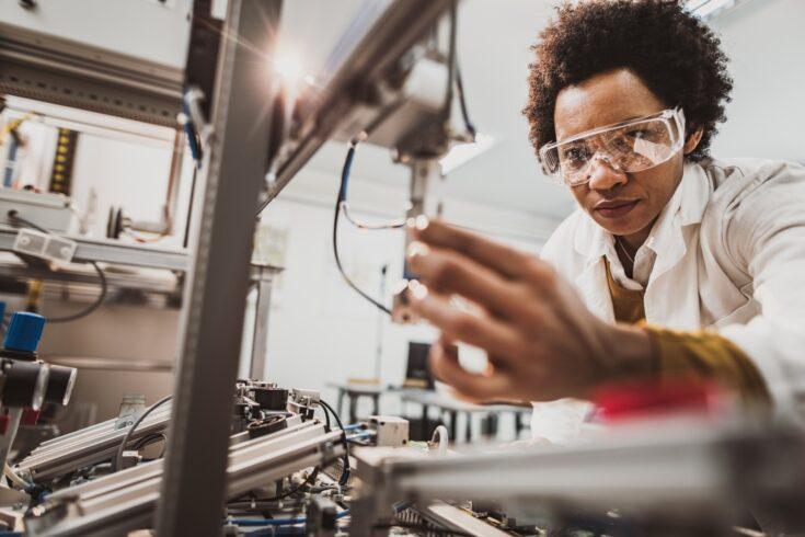 Black female engineer working on industrial machine in a laboratory