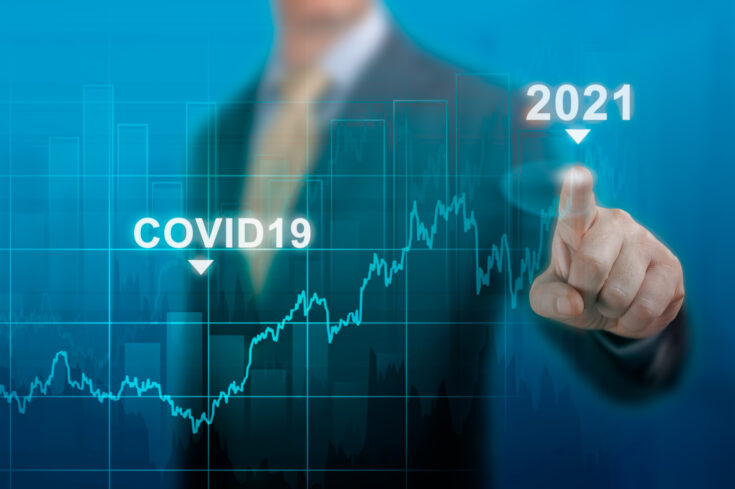 global economy concept of economic recovery after the fall due to the covid 19 coronavirus pandemic. Businessman pointing graph corporate future growth plan on dark blue