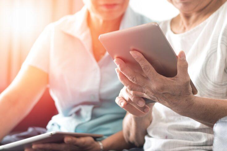 Ageing elderly women using tablet.