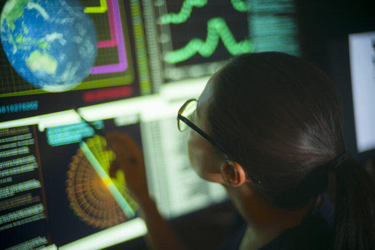 Asian woman staring at a screen with Earth displaying