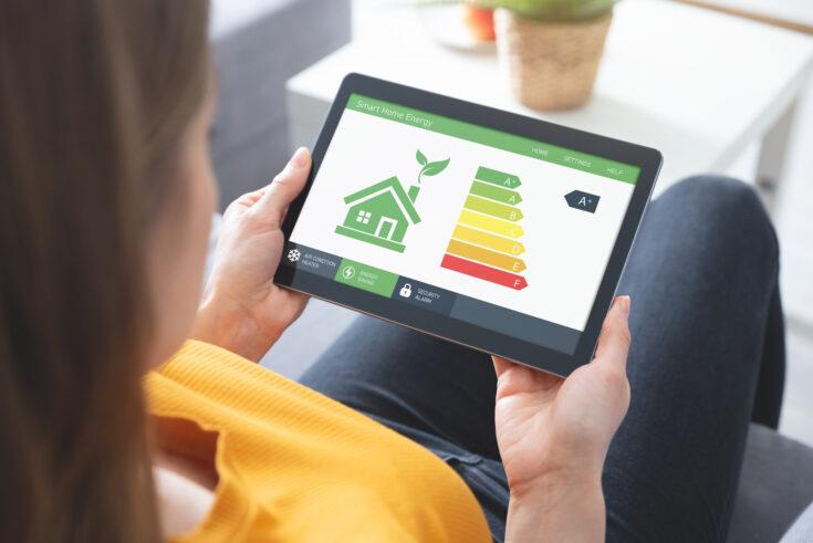 Energy efficiency mobile app on screen, eco house